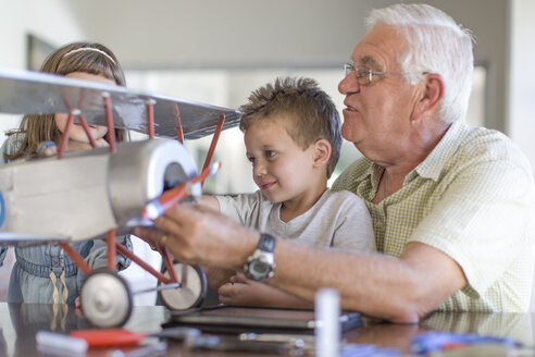 Grandfather and grandchildren building up a model airplane - ZEF004853