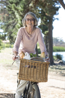 Portrait of senior woman on bicycle - ZEF004743