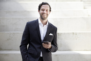 Smiling businessman with smartphone in a modern building - FMKF001519