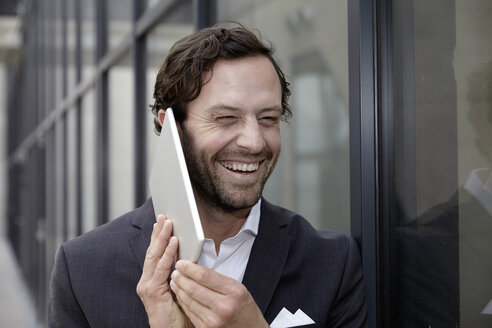 Portrait of laughing businessman trying to phone with his digital tablet - FMKF001557