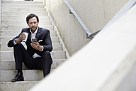 Businessman with coffee to go using smartphone in a modern building - FMKF001525