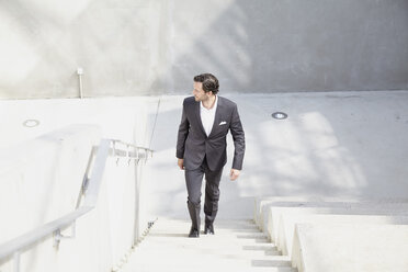 Businessman going upstairs in a modern building - FMKF001533