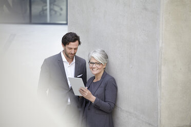 Two business people with digital tablet in modern architecture - FMKF001563