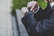Businessman checking smart watch - UUF004114