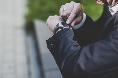 Businessman checking smart watch - UUF004114