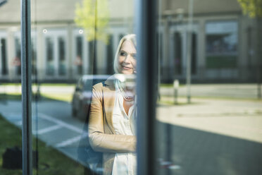 Mature woman looking at mirrored self at window pane - UUF004119