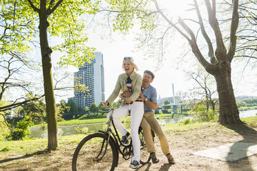Mature couple riding bike in park, man sitting on rack - UUF004123