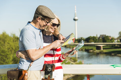 Germany, Mannheim, Mature couple taking city break, looking at map - UUF004127
