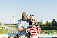Germany, Mannheim, Mature couple taking city break, looking at map - UUF004128