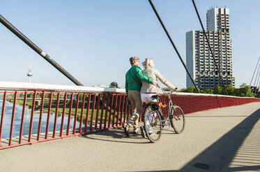 Germany, Mannheim, Mature couple crossing bridge, pushing bicycle - UUF004143