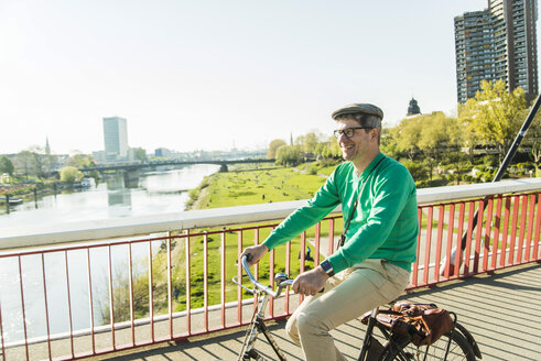 Germany, Mannheim, Mature man cycling over bridge - UUF004144