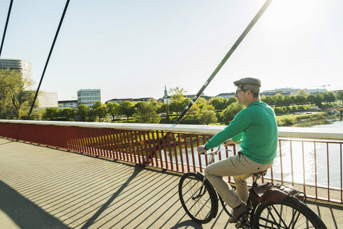 Germany, Mannheim, Mature man cycling over bridge - UUF004145