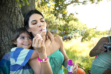 Mother with son at tree blowing soap bubbles - TOYF000293