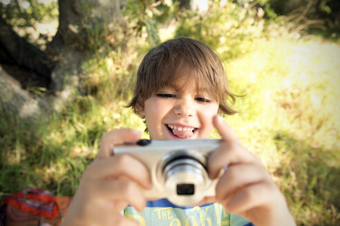 Smiling boy with camera outdoors - TOYF000253