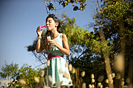Girl blowing soap bubbles outdoors - TOYF000256