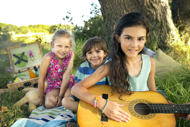 Girl at tree holding guitar with siblings in background - TOYF000262