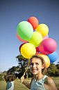 Smiling girl holding bunch of balloons outdoors - TOYF000265