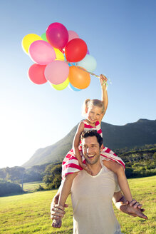 Happy father carrying daughter with balloons on shoulders - TOYF000268