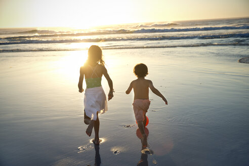 Boy and girl running on beach at sunset - TOYF000277
