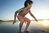 Boy playing on beach at sunset - TOYF000285