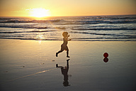 Boy running on beach at sunset - TOYF000287