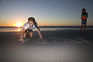 Girl on the beach at sunset drawing in sand - TOYF000290