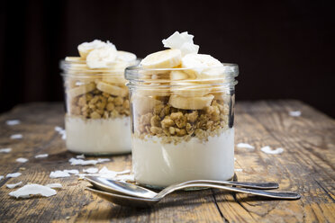 Glasses of natural yoghurt, granola, banana slices and coconut flakes - LVF003313