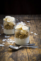 Glasses of natural yoghurt, granola, banana slices and coconut flakes - LVF003314