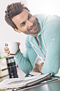 Portrait of man with cup of coffee and newspaper in the kitchen - MADF000237