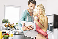 Couple using digital tablet in the kitchen - MADF000251