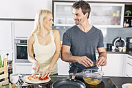 Couple preparing scrambled eggs together in the kitchen - MADF000227