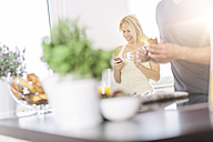 Couple having breakfast in the kitchen at weekend - MADF000272