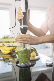 Smiling young woman preparing smoothie in the kitchen, close-up - MADF000284
