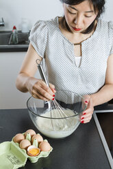 Woman stirring dough in a glassbowl with wire whisk - FLF001028