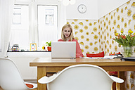 Young woman using laptop at her home office - RHF000830
