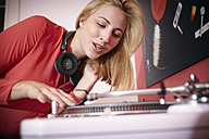 Smiling young woman with headphones and record player at home - RHF000857