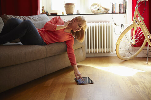 Young woman with digital tablet lying on couch at home - RHF000834