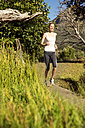 Smiling woman jogging in rural landscape - TOYF000593