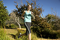 Smiling woman jogging in rural landscape - TOYF000332