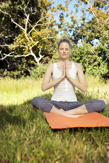 Woman practising yoga in a meadow - TOYF000338