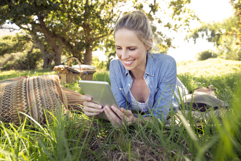Smiling woman with digital tablet lying on meadow - TOYF000359