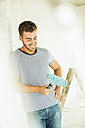 Smiling young man renovating holding paint roller - UUF004161