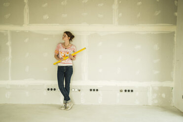 Young woman renovating standing at blank wall - UUF004170