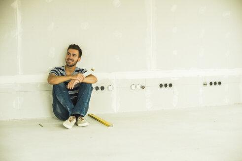 Young man renovating sitting at blank wall - UUF004183