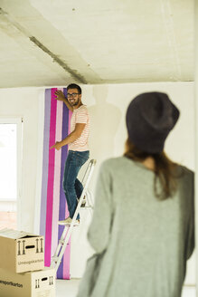 Young man renovating showing wallpaper to woman - UUF004221