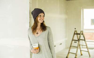 Smiling young woman having a coffee break from renovating - UUF004225