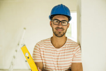 Portrait of smiling young man wearing hard hat - UUF004229
