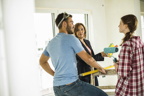 Three people renovating and discussing - UUF004231