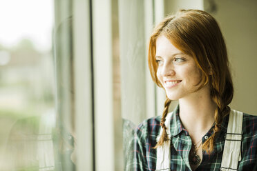 Smiling young woman looking out of window - UUF004240