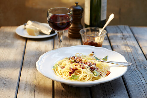 Dish of spaghetti with tomato pesto and grated parmesan and glass of red wine - KSWF001478